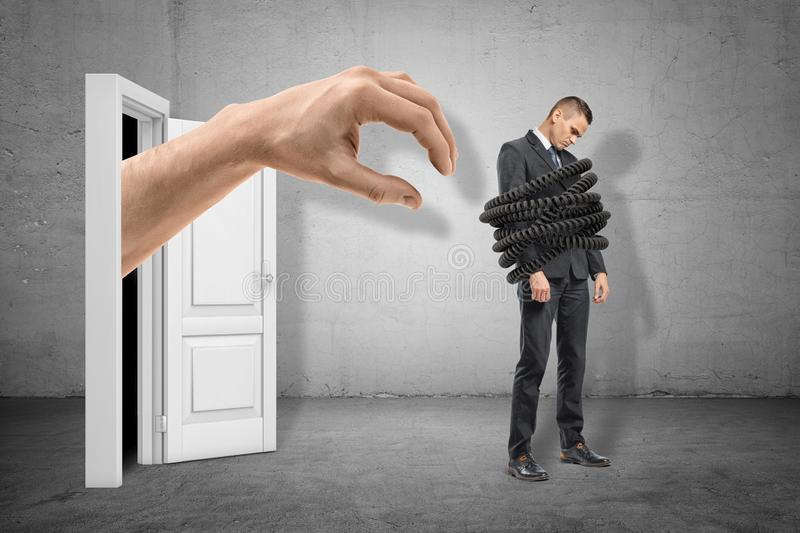 Big hand reaching to young sad businessman tied up with telephone cord on grey wall background royalty free stock photos