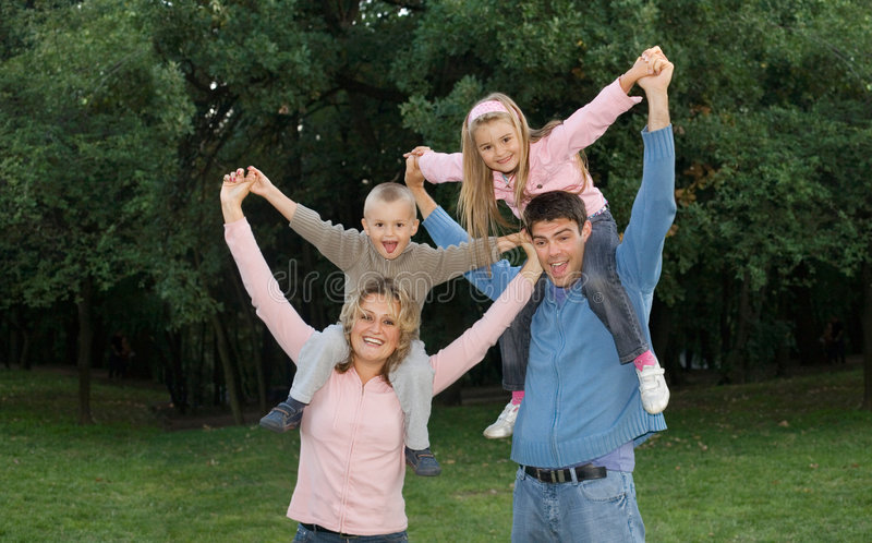 Big happy family. Young couple with children playing outside stock photos