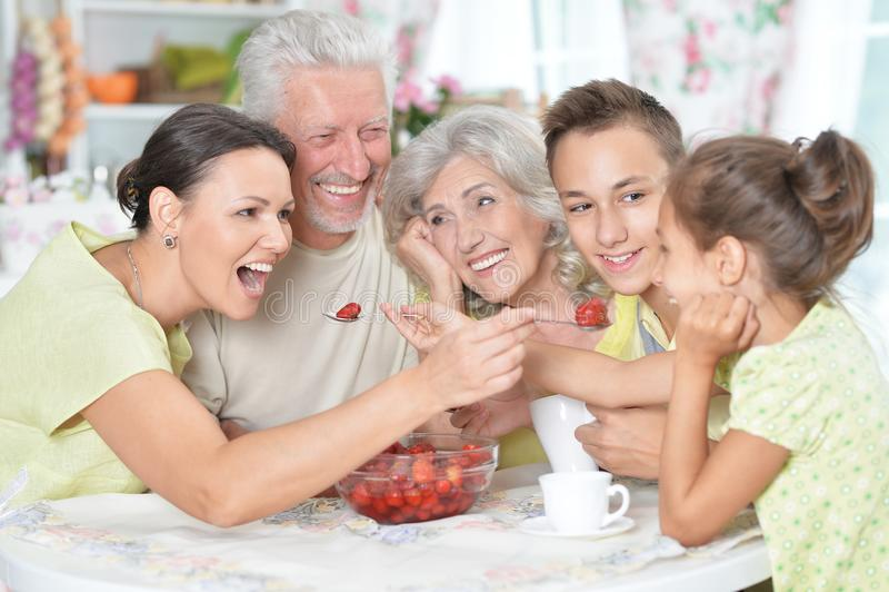 Big happy family eating. Fresh strawberries at kitchen royalty free stock photo