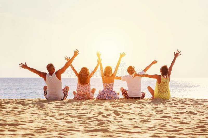 Big happy family or friends having fun against sunset beach royalty free stock image
