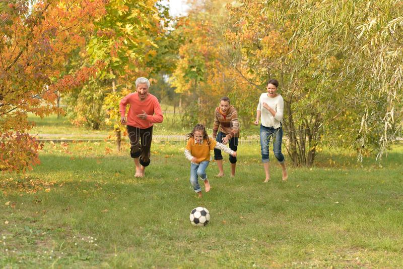 Big happy family playing football in autumn park stock photos