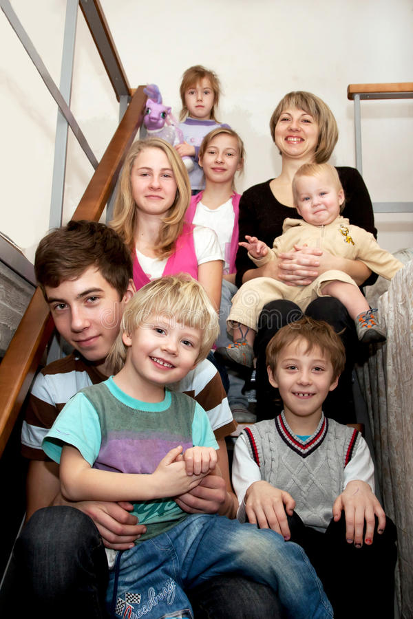Big happy family sitting on the stairs at home. stock photo