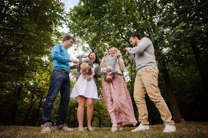 Big and happy smiling family playing with children in park stock image