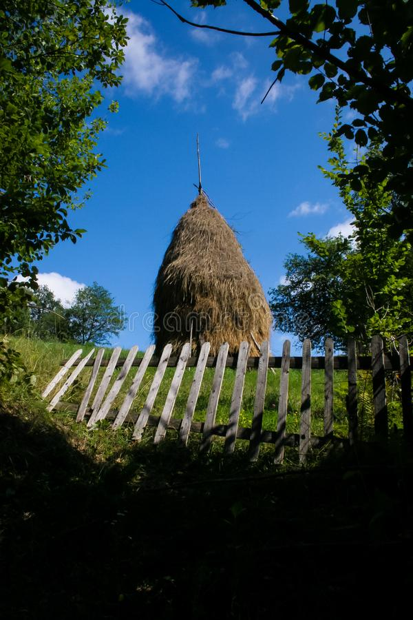 Big Haystack On the Field Behind the Fence. Big haystack behind the fence on the field in Carpathian mountains royalty free stock image