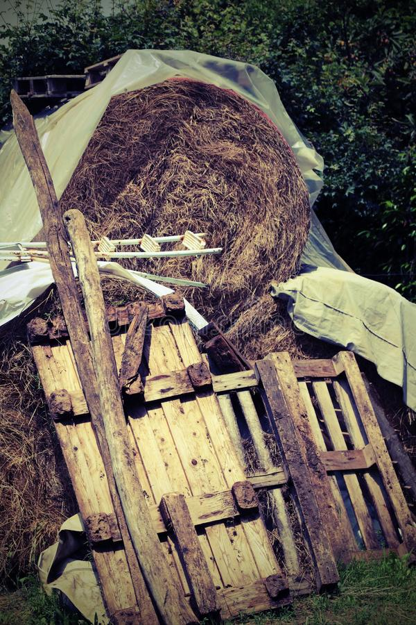 Big haystack with wooden pallets in the farm. With old toned effect stock image
