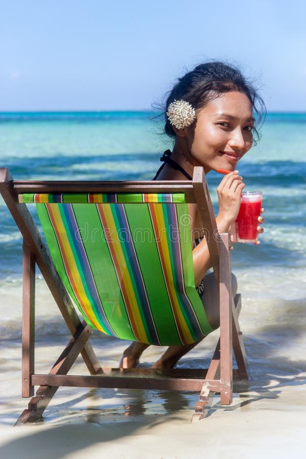 Big head woman sitting on a deck chair on the sea beach. Ethnic girl with a white flower in her hair relaxed by the sea with red juice. Beautiful woman sitting stock photos