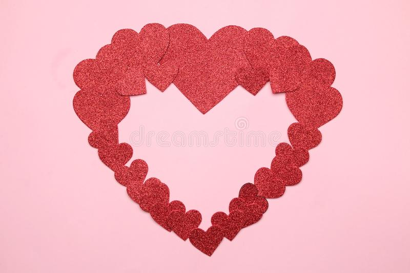 A big heart of small red hearts on a bright pink background. frame of hearts, top view with space for text stock images