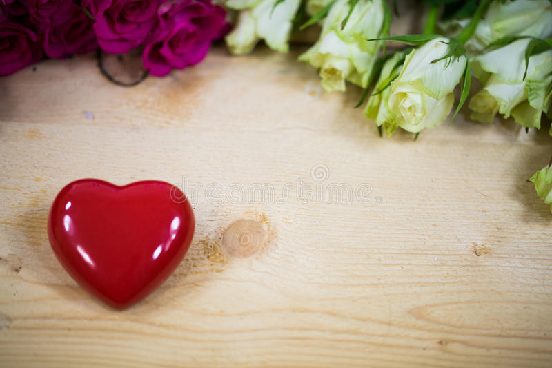 Big heart on a wooden background. Red roses royalty free stock photos