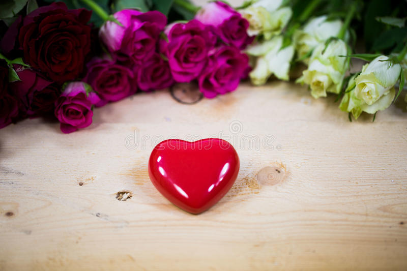Big heart on a wooden background. Red roses stock image