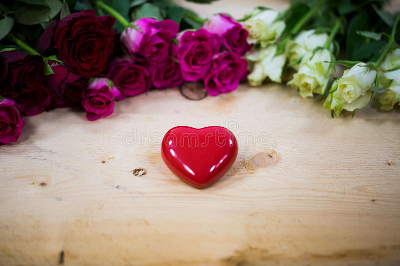 Big heart on a wooden background. Red roses stock photo