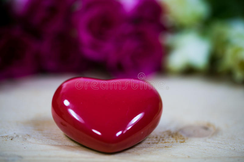 Big heart on a wooden background. Red roses royalty free stock image