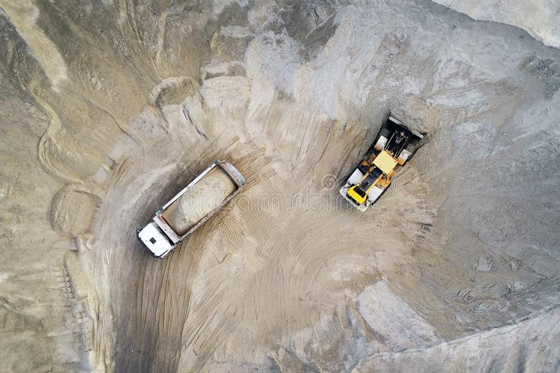 Big heavy wheel loader loading sand into dump truck in sand pit. Heavy industrial machinery concept royalty free stock image