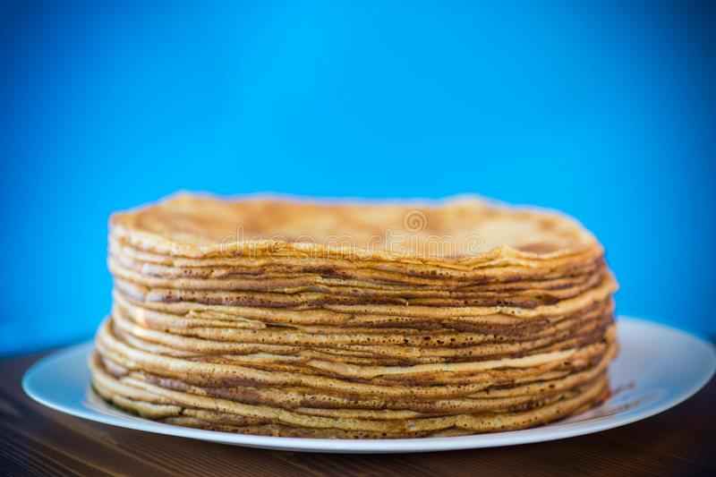 Big high stack of thin pancakes in a plate royalty free stock photos