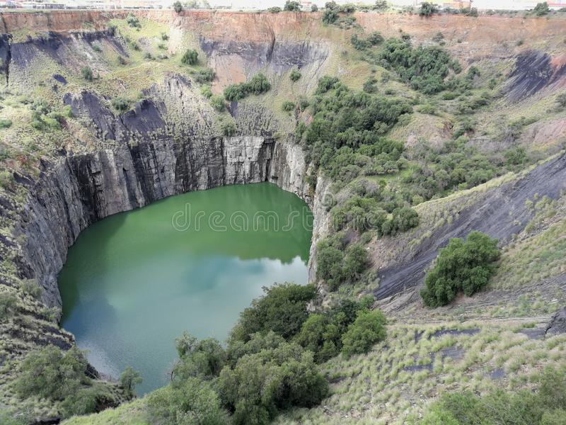 The Big Hole at Kimberly. The Big Hole landmark at Kimberly in South Africa filled with green water and surrounded by rocks and shrubbery stock photography