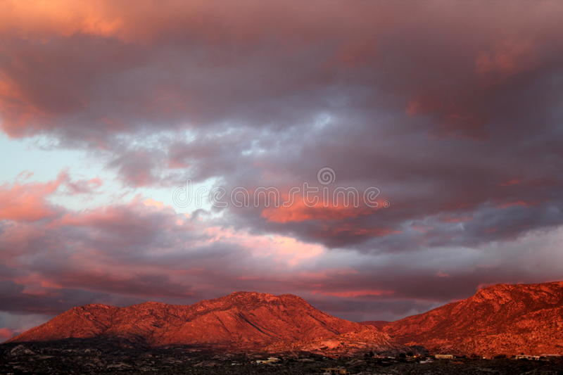 Big huge sunset clouds over the red mountains in Tucson Arizona. Desert mountain sunset. Sunset heavily saturated with color. Dramatic red sunset over the Tucson royalty free stock image