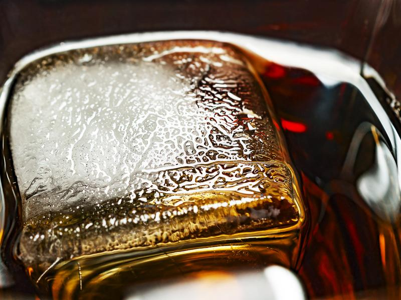 Big Ice Cube in a Glass of Whiskey and Coke Drink. Ice Texture Details stock image