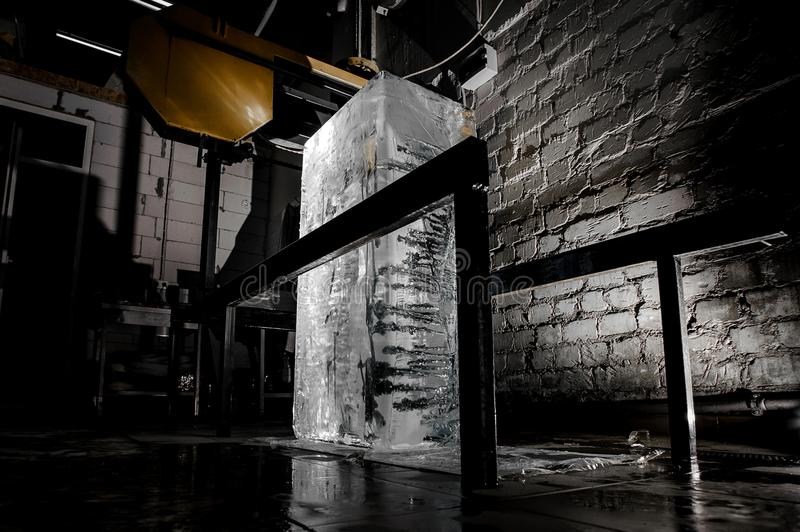 Big ice cube standing on the floor on the ice production plant. Big clear ice cube standing on the floor on the ice production plant in the dark with the one royalty free stock photography