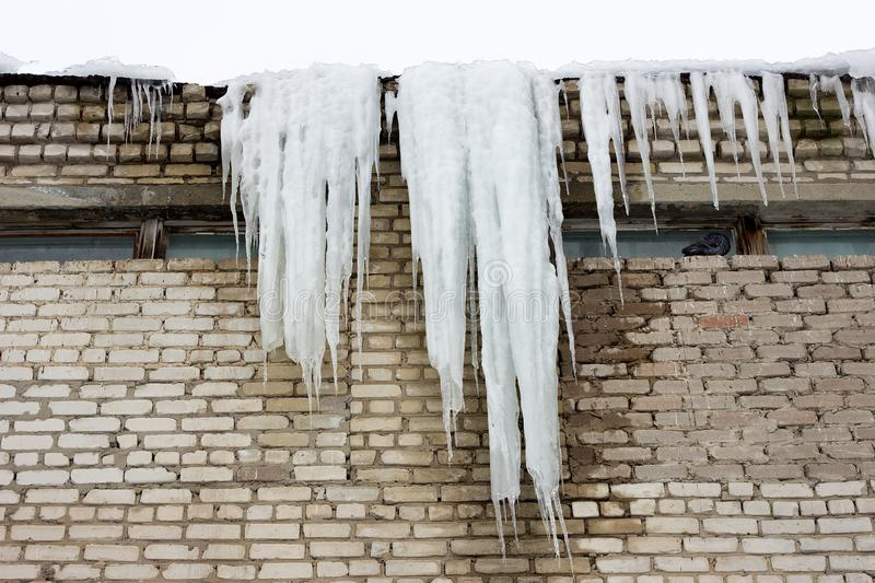 Big icicle on the roof of a building royalty free stock photography