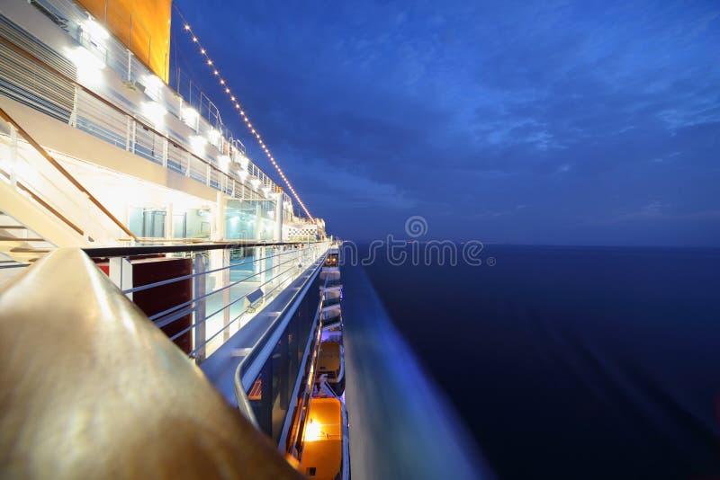 Big illuminated cruise ship riding in evening. royalty free stock image