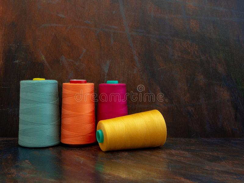 Big industrial cones of orange, teal and yellow sewing threads laying and standing on a dark background. Front view studio shot. royalty free stock images