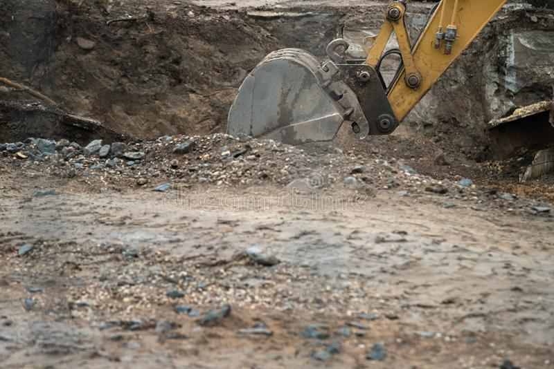 Big industrial excavator digging up ground, urban development. Bulldozer scoop working in construction site royalty free stock photography