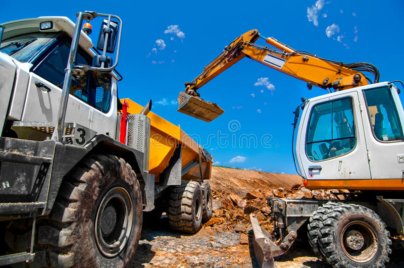 Big, industrial excavator on new construction site stock image