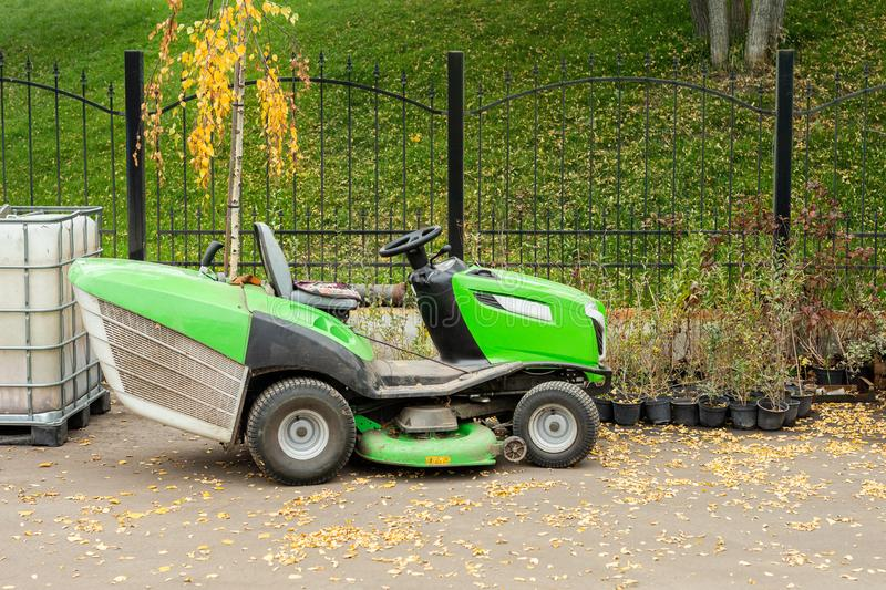 Big industrial lawnmower machine standing at parking in city park. Green lawn grass mower tractor at municipal street service area royalty free stock photos