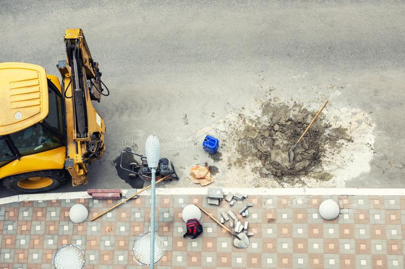 Big jackhammer drill drilling road.Heavy machinery crushing asphalt for stormwater drain repair royalty free stock images