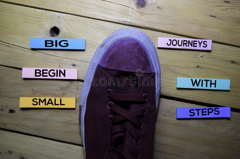 Big Journeys Begin With Small Steps text with sneaker on sticky Notes isolated on table desk background stock photos