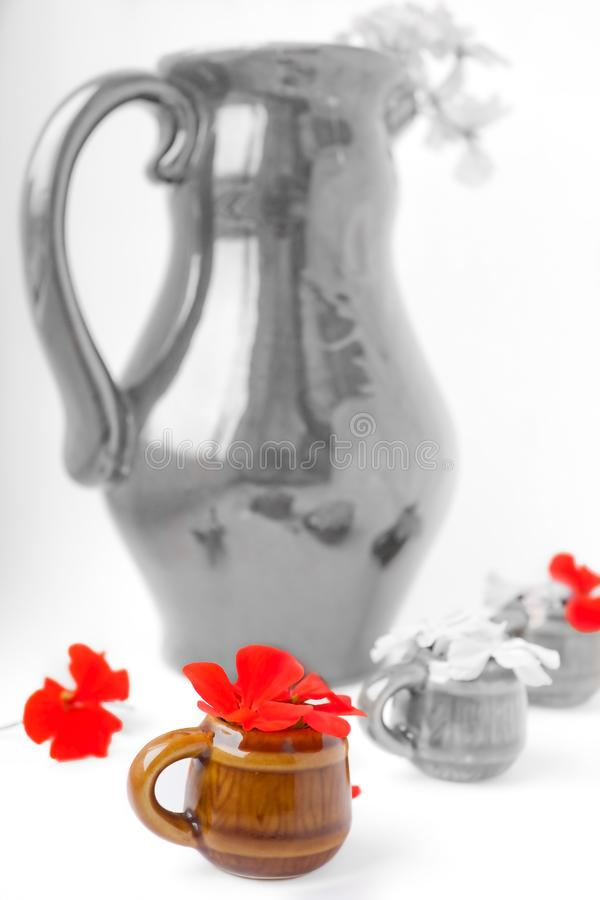 Download The Big Jug With Geranium And Mugs Stock Image - Image of comparison, crowd: 13915707
