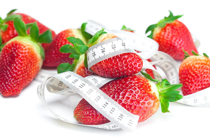 Big juicy red ripe strawberries and measure tape royalty free stock photography