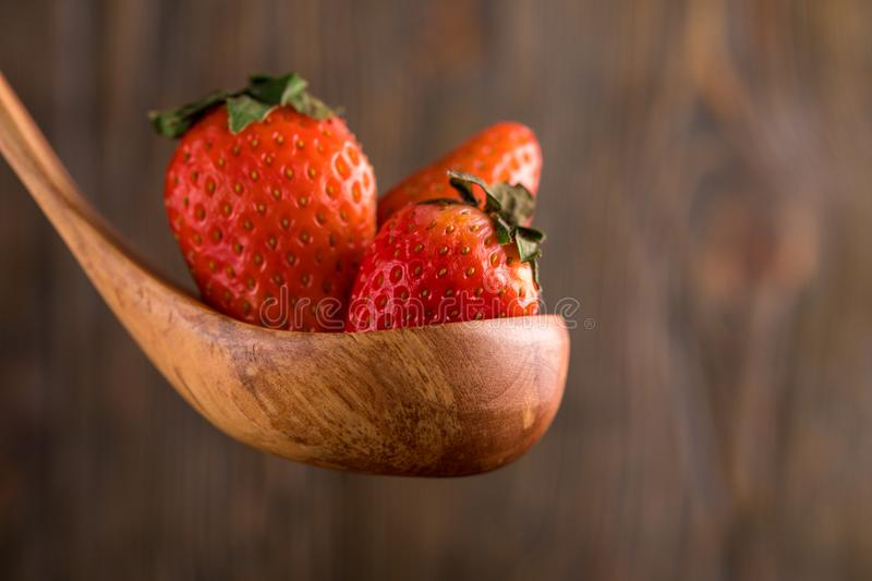 Big juicy strawberries in a wooden spoon on a wooden background. Macro. royalty free stock photo