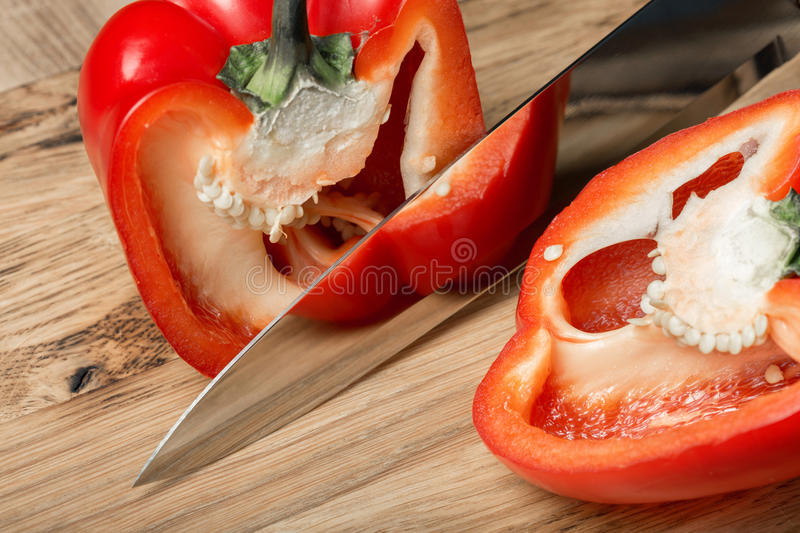 Big kitchen knife cut a bell pepper on two parts. Close up royalty free stock photo