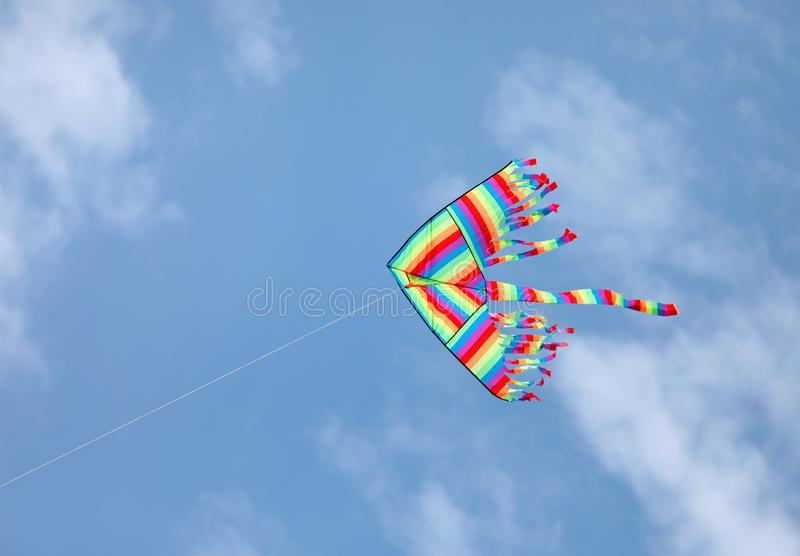 Big kite with many colors. On the blue sky stock image