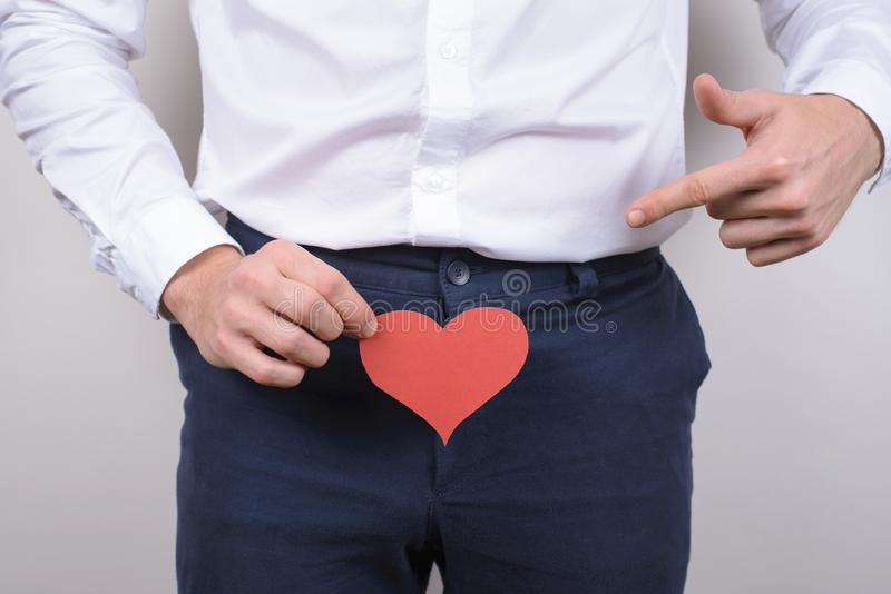 Big large long pleasure intimate intimacy size concept. Cropped close up photo portrait of handsome happy smiling satisfied. Gentleman showing holding heart stock photo