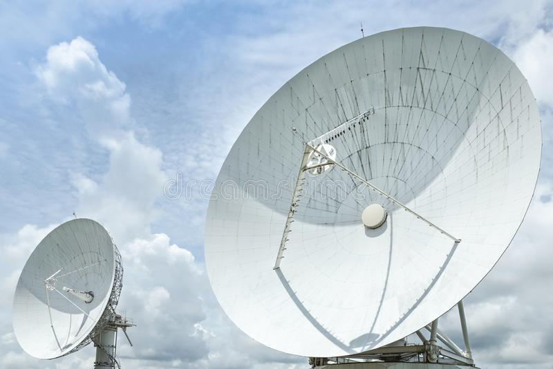 Big large white satellite dishes turn up skyward on blue sky royalty free stock photos