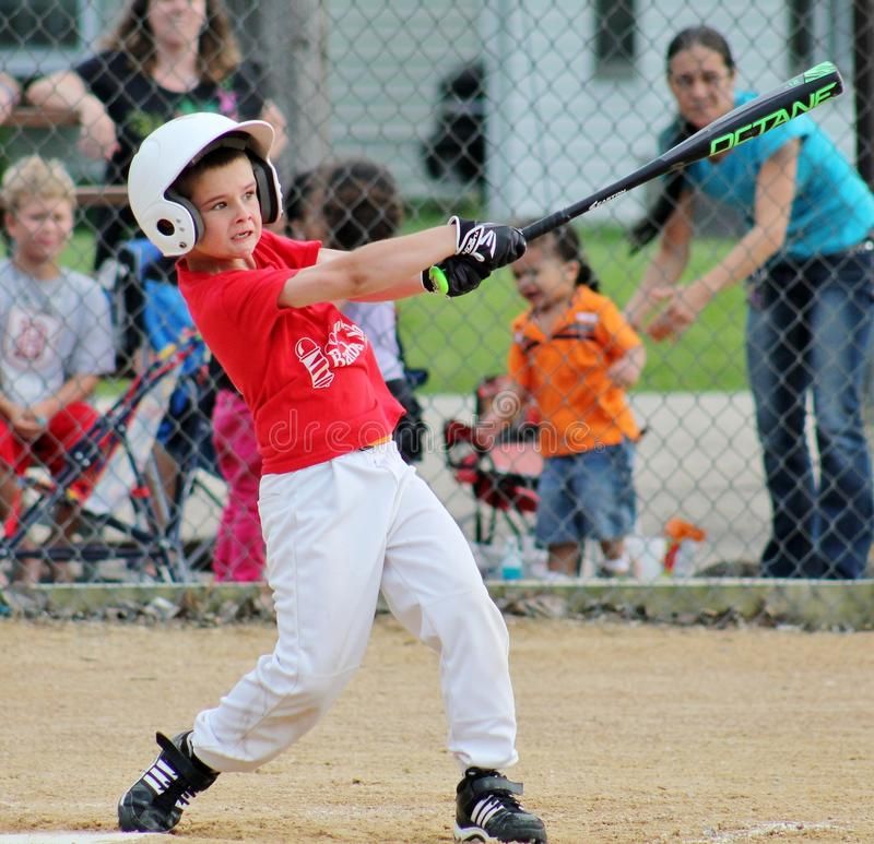 The Big League Stare and Swing. Young boy swinging the bat at a little league baseball game with determined facial expression. Picture taken at Oliver Thomas stock images