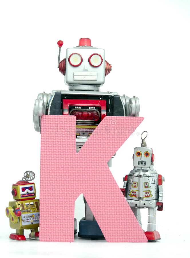 Big letter pink K held by vintage robot toys. Capital letter pink K held by vintage robot toys on white royalty free stock images