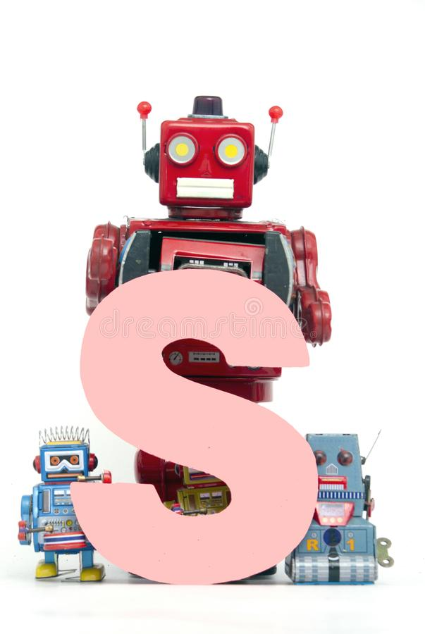 Big letter pink S held by vintage robot toys. Capital letter pink S held by vintage robot toys royalty free stock photos
