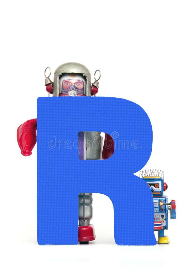 Big letter R held by vintage robot toys. Capital letter blue R held by vintage robot toys on white stock photos