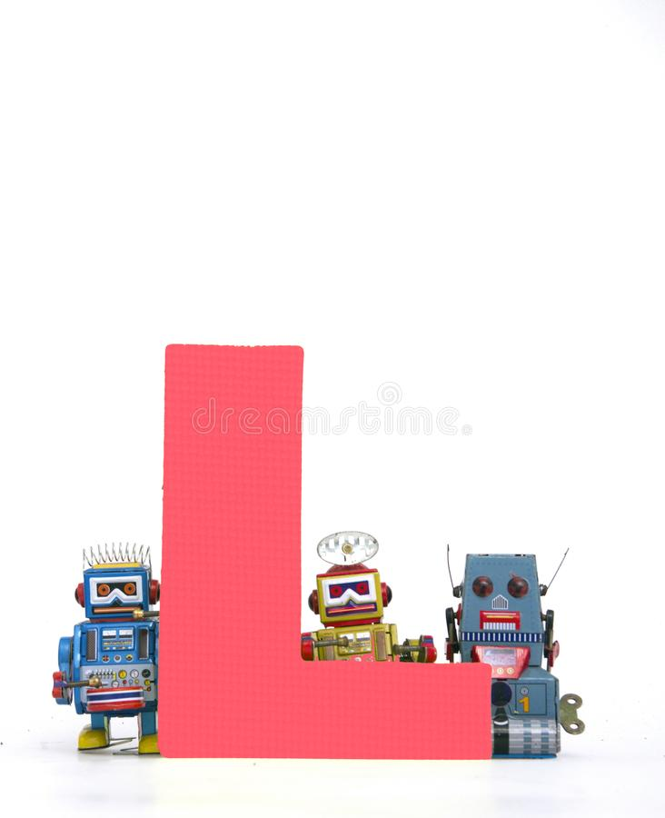 Big letter red L held by vintage robot toys. Capital letter red L held by vintage robot toys on white royalty free stock photography