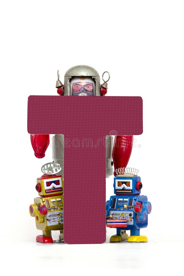Big letter T capital letter T held by vintage robot. Capital letter T held by vintage robot toys stock photography