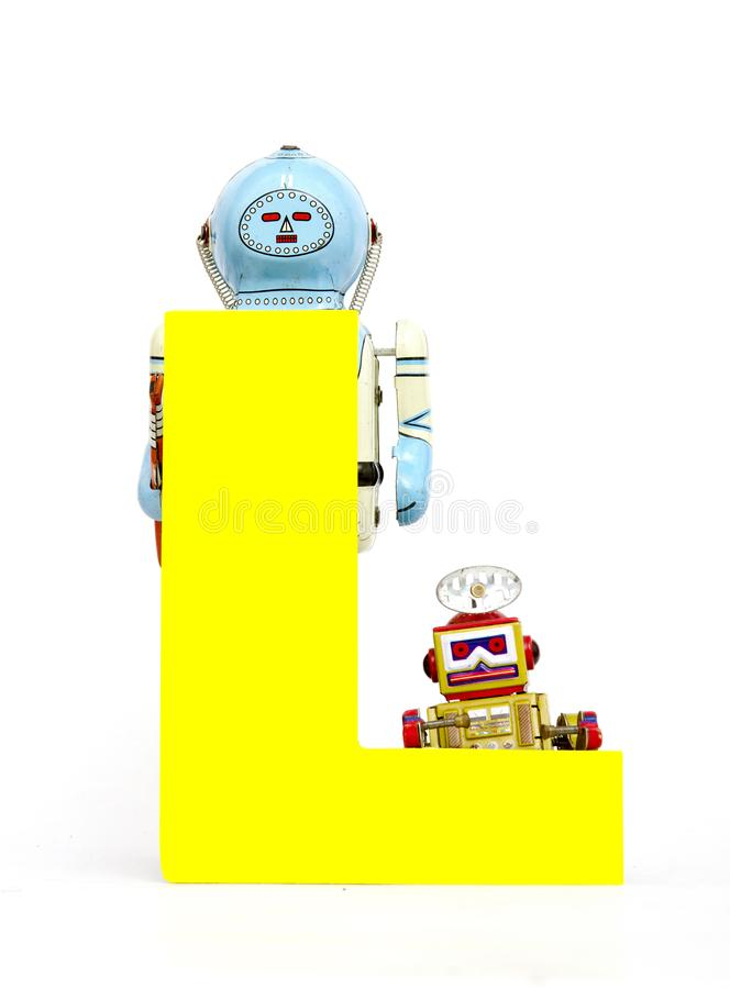 Big letter yellow L held by vintage robot toys. Capital letter yellow L held by vintage robot toys on white royalty free stock image