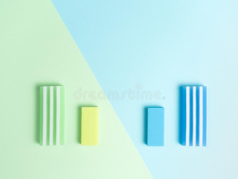 Big and little green eraser and blue eraser on green and light blue background.  royalty free stock photography