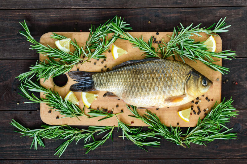 Download Big Live Carp Crucian On A Cutting Board With Rosemary Branches. Stock Image - Image of meal, dinner: 91842355