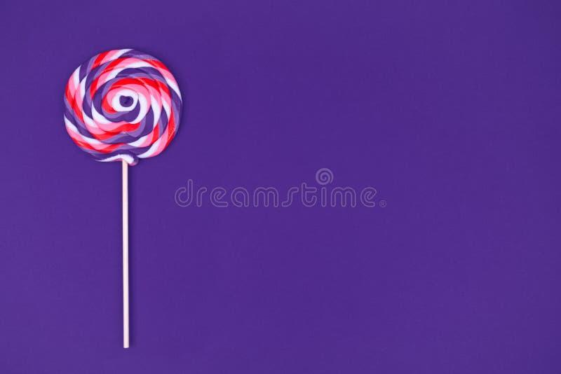 Big lollipop on solid ultra violet background. Horizontal stock images