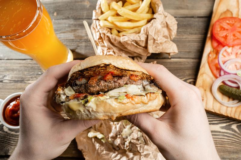 Big lunch. Burger with beef BBQ and fries. Glass of beer on a wooden background. The concept of fast food and unhealthy. Food royalty free stock photos