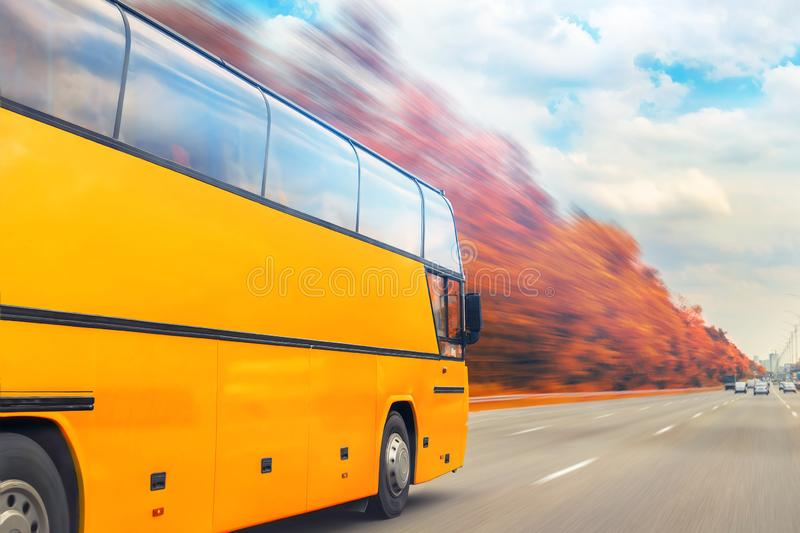 Big luxury comfortable tourist bus driving through golden autumn tree highway on bright sunny day. Blurred motion.Travel and coach. Big luxury comfortable stock photography
