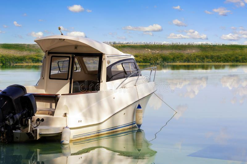 Big luxury fishing boat with cabin moored near river or lake shore in still water. Blue sky on the background. Summer adventure, stock photo