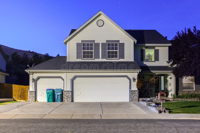 Big luxury house with triple garage doors at dusk, night in suburbs royalty free stock images